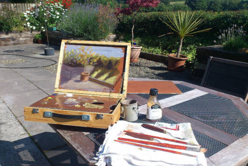 Painting with a pochade box outside in the garden