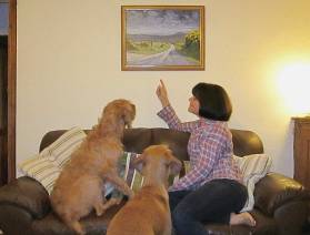 Happy client with their dogs and their painting hanging on the wall